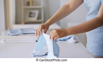 pregnant woman folding baby boys clothes at home 27 -...