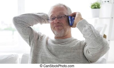 happy senior man calling on smartphone at home - technology,...