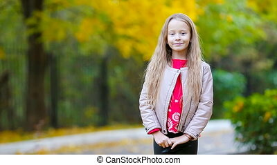 Portrait of adorable little girl in fall looking at camera...