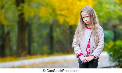 Portrait of sad little girl in fall looking at camera and...