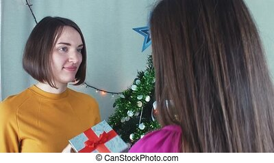 Two cheerful girls giving Christmas presents t and opening them with gratefully