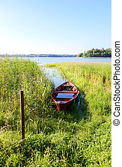 Old red wooden fishing boat with water at the lake in summer...