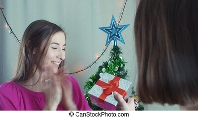 Two cheerful girls giving Christmas presents opening them...