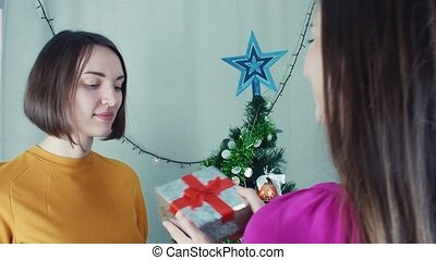 Two cheerful girls giving Christmas presents opening them with disappointment