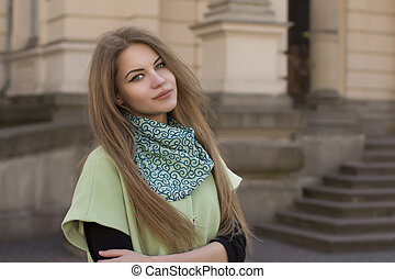 Smiling young woman in a green coat