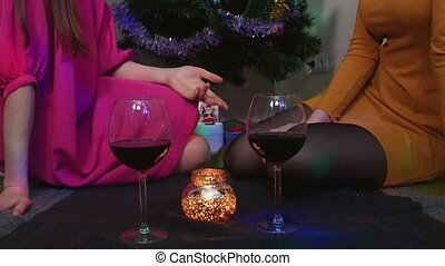 Young female couple sitting near Christmas tree with glasses of wine having fun