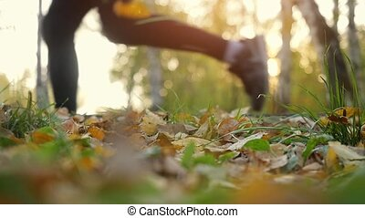 Young men are running on fallen autumn leaves in the forest...