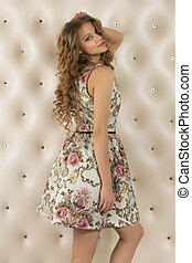 Attractive young woman in dress against a white wall