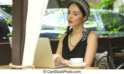 Woman working on laptop in cafe and answering the call,...