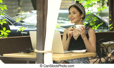 Woman working on laptop in cafe and drinking coffee,...