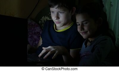 children boy and girl playing in the laptop at night online...