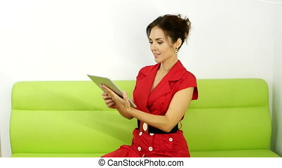 Young girl with tablet pc on the sofa - Elegant bussines...