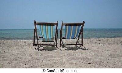 Two lounge chairs on a beach
