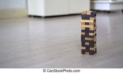 Hand destroying Jenga Tower in the room.