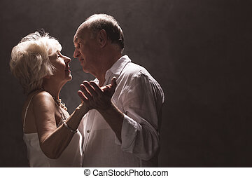 Senior couple dancing - isolated on dark background