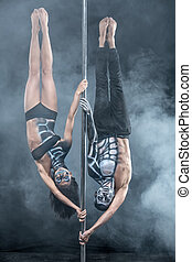 Posing of pole dance couple in dark studio - Image of the...