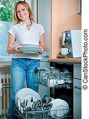 Dishwashing - young woman loading dishes to the dishwasher
