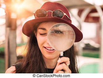 Beautiful girl with magnifying glass - Funny young woman...