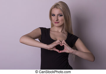 Young woman showing a heart by her fingers