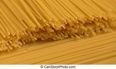 Raw yellow long spaghetti.Thin pasta arranged in rows.