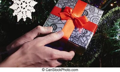 Male hands putting gift on decorated Christmas tree close up