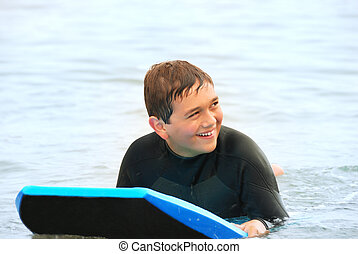 Smiling Teen Surfer - Smiling teenage surfer laying on his...