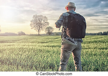 man travelling in nature with backpack - Portrait of a white...