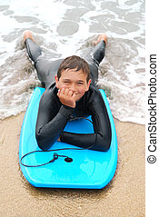 Smiling Teenage Surfer - Smiling teenage surfer in a wetsuit...