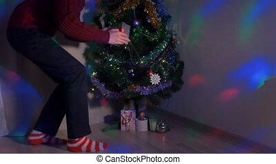 Young man sneaking up to Christmas tree and placing a gift...