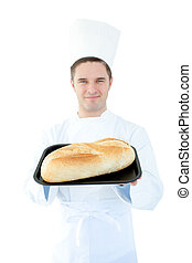 Smiling male cook holding a bread into the camera