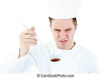 Young male chef tasting a soup with distorted face against...