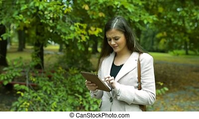 Beautiful young woman with tablet against green city park -...