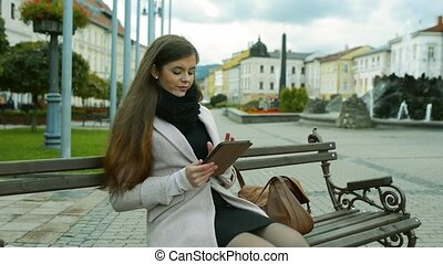 Woman working on tablet sitting on bench in old town -...