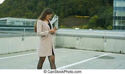 Beautiful woman in the city working on tablet - Beautiful...