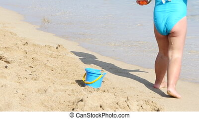 Little girl in blue swimsuit playing on the beach