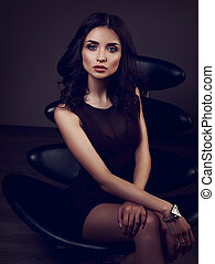 Sexy young model in brown dress sitting on the black chair on dark shadow with fashion watch on the hand background. Toned portrait