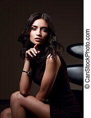 Sexy young model in brown dress sitting on the black chair on dark shadow with fashion watch on the hand background