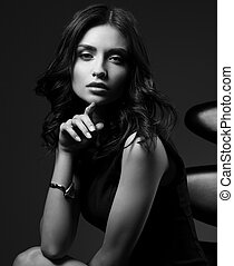 Sexy young model in brown dress sitting on the black chair on dark shadow with fashion watch on the hand. Black and white closeup portrait