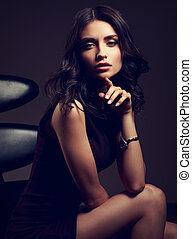 Sexy young model in brown dress sitting on the black chair...