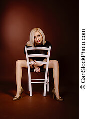 Young blonde woman on a chair