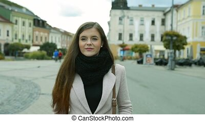 Woman in autumn coat walking outdoors in old town -...