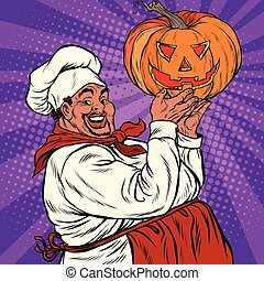 African American or Latino cook with a Halloween pumpkin,...