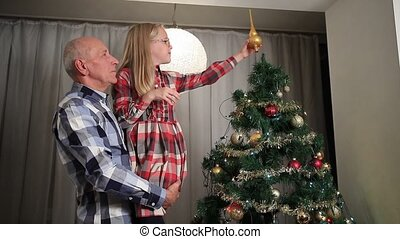 Sweet little girl adjusting Christmas tree top.