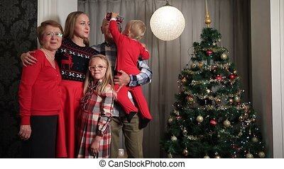 Happy family on Christmas Eve by Xmas tree - Smiling multi...