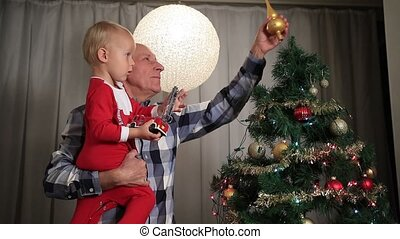 Grandfather with boy decorating christmas tree