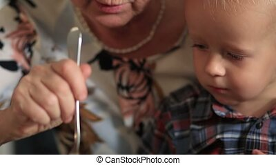 Grandmother feeding her little baby grandson - Close up of...