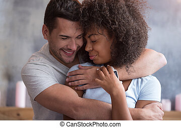 Delighted couple cuddling together in love.