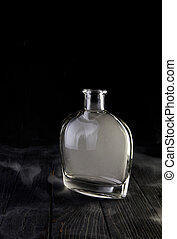 Empty decanter with smoke on black background