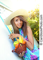 Beautiful girl holding a basket of fruit