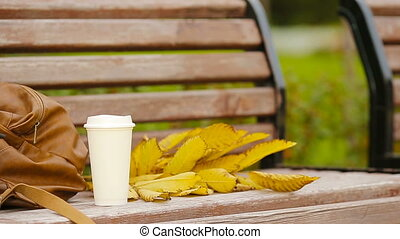 Cup of hot coffee and yellow autumnal leaveas on the park...